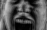 A black and white photograph of a woman screaming.