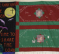 """The quilt section is made of three rectangular panels. One is tall and the other two are long and stacked one on top of the other. The two panels at the right feature alternating red and green fabric. There is a picture of a man's face at the center of each, surrounded by text and smaller images. The tall panel to the left is a figure on a black background whose hand is raised to a series of birds who fly towards a full moon with a cross on it. The panel included large text that reads, """"After carrying the Burden Time to Share the Load"""" in red script. The figure is sitting on a semicircular item with """"Cleveland VA"""" written on it."""