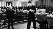 """A black and white still image from the movie, """"Mr Smith Goes to Washington"""" Where the actor James Stewart stands in the floor of senate, overwhelmed and gripping hand fulls of paper."""